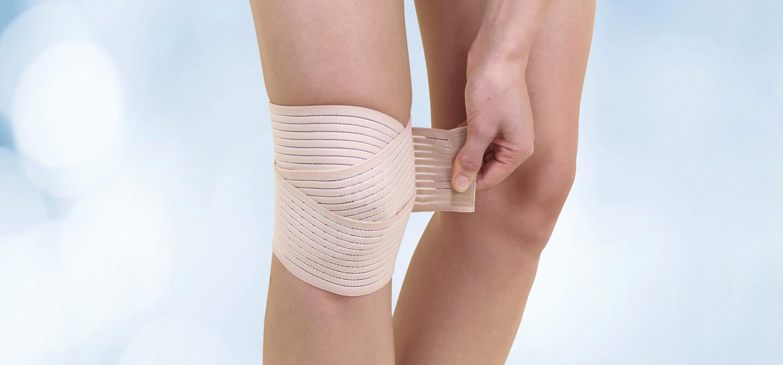 Eine Frau legt sich eine Kniebandage an