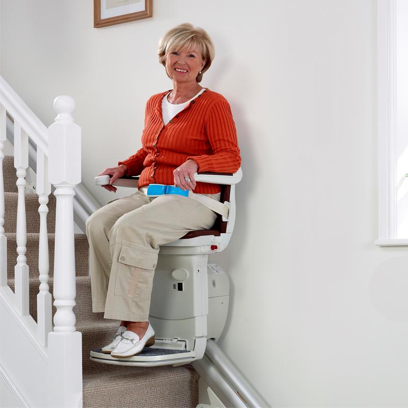 Ältere Dame benutzt einen Treppenlift.