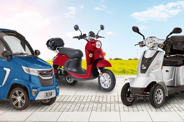 Es sind verschiedene Arten von Elektromobilen abgebildet: Ein blaues Kabinenfahrzeug, daneben ein rotes Dreirad-Elektromobil und ein silbernes Vierrad-Elektromobil.