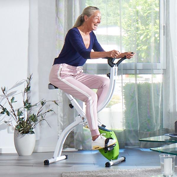 Frau höheren Alters trainiert zuhause auf einem Fitnessgerät.