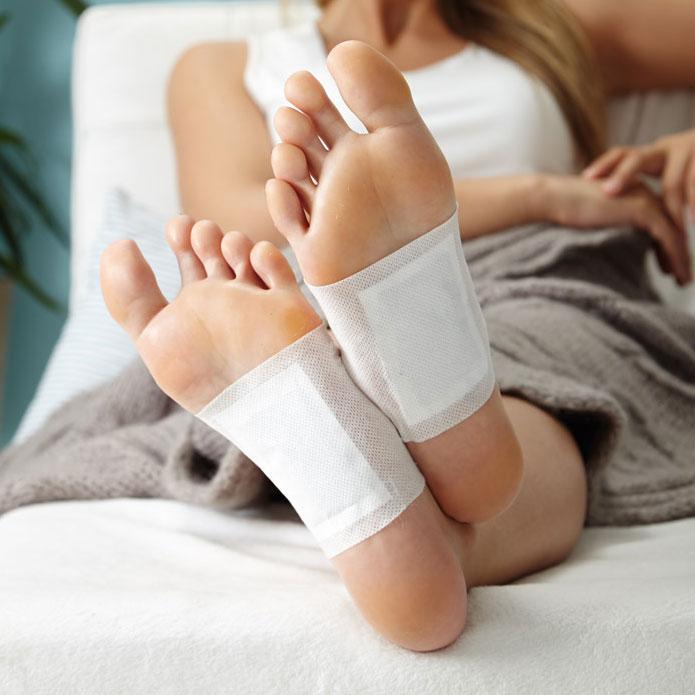 Frau pflegt ihre Füße mit Fußpads, die an der Unterseite ihrer Füße kleben