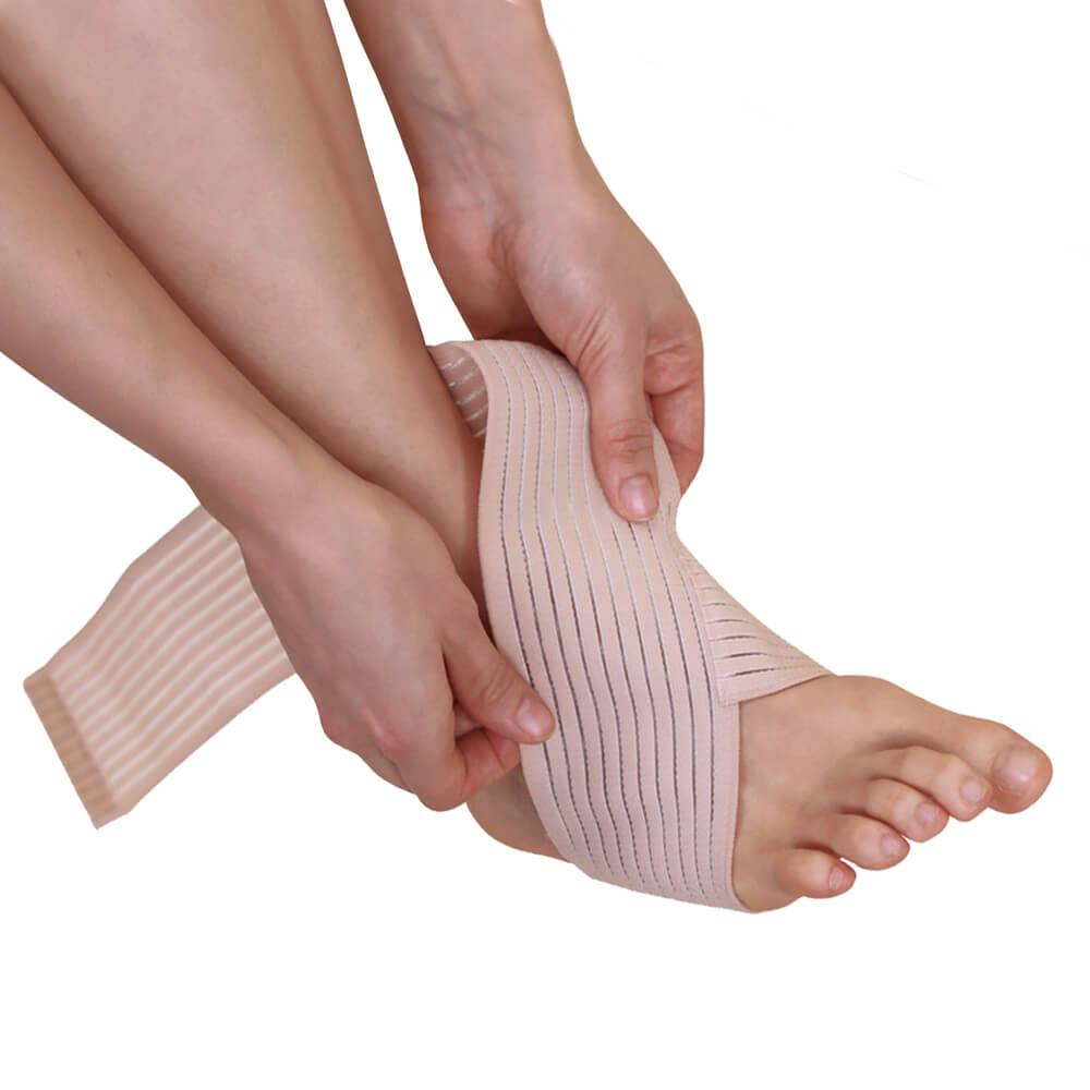 Frau legt sich eine Fußbandage um den Fuß.