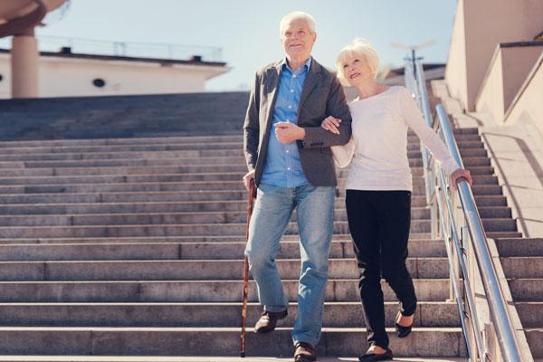 Älteres Ehepaar geht lächelnd eine Treppe hinunter. Der Mann benutzt einen Gehstock, um sich zu stützen.