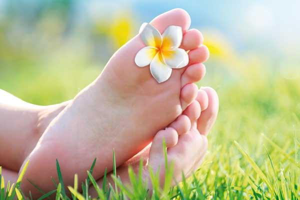 Füße einer jungen Dame mit Wiesen-Hintergrund. Zwischen ihren Zehen klemmt eine Blüte.