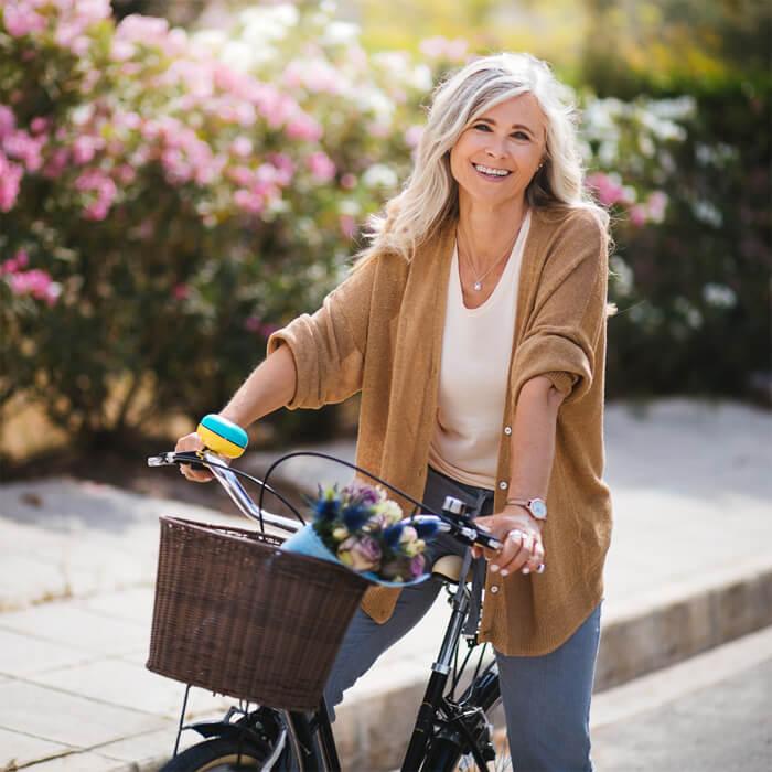 Eine Frau mittleren Alters hat Spaß an ihrem E-Bike.