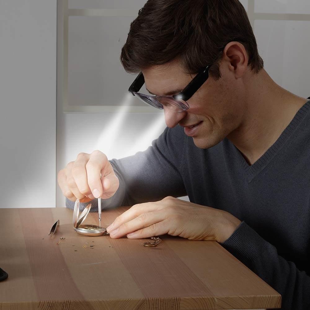 Junger Erwachsener benutzt eine Vergrößerungsbrille um sich beim Handwerk besser konzentrieren zu können.