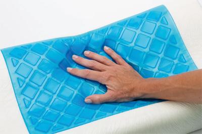 Eine Hand visualisiert die Druckentlastung bei einem visko-elastischen Kissen mit Geleinlage