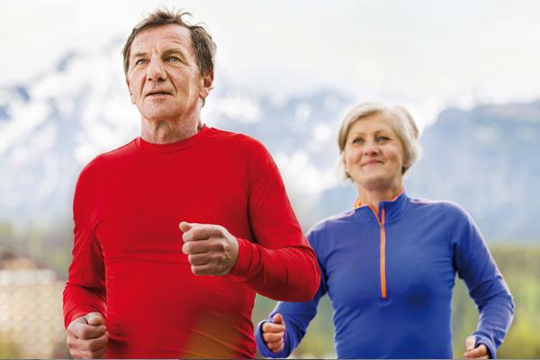 Älteres Ehepaar joggt gemeinsam durch die Natur und hält sich fit.