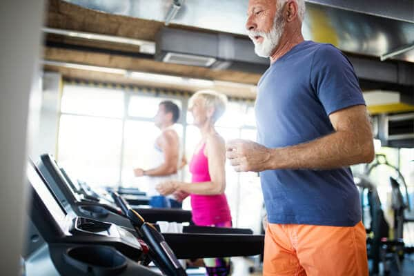 Ein beleuchteter Raum eines Fitnessstudios, wo verschiedene Arten von Fitnessgeräten zu sehen sind.