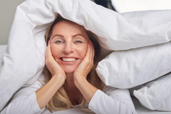Frau mittleren Alters liegt zwischen ihrer Bettwäsche und lächelt den Betrachter an.