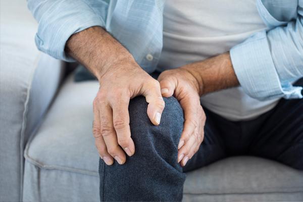 Mann fasst sich mit beiden Händen ans Knie, da er Knieschmerzen zu haben scheint.